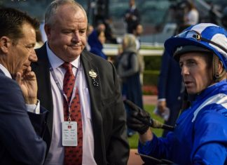 Mike de Kock and assistant trainer Trevor Brown receive advice from jockey Jim Crowley after the Jebel Hatta.
