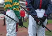 Jockeys with whips.