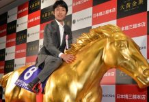 "Japanese leading jockey Yutaka Take poses on a life-sized statue of the Japanese legendary ""Oguri Cap"" horse, which won four grade-one (G1) races and died in 2010, made from fiber rainforced plastic (FRP) and coated with gold foil is displayed at the opening of the Gold Expo event at Tokyo's Mitsukoshi department store on July 11, 2013. The exhibition will display and sell a total of 100 million USD (10 billion yen) gold made products, including the gold horse, priced at 201,400 USD (20.14 million yen). AFP PHOTO / Yoshikazu TSUNO"